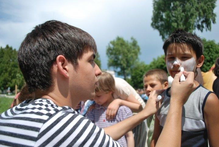 Projects Abroad volunteer with children in Romania paints a child's face during an outdoor activity at a Childcare placement.